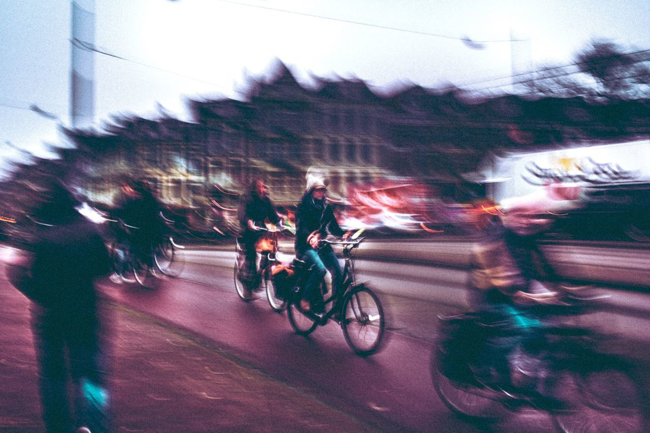 blurred motion, speed, motion, sports race, riding, transportation, road, real people, land vehicle, competition, bicycle, mode of transport, outdoors, sport, men, group of people, competitive sport, day, motorcycle, racing bicycle, architecture, sports clothing, sports track, city, sportsman, sky, people