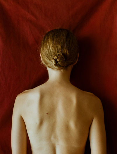 Rear view of shirtless young woman standing against red wall. uncertainty, love, mental health