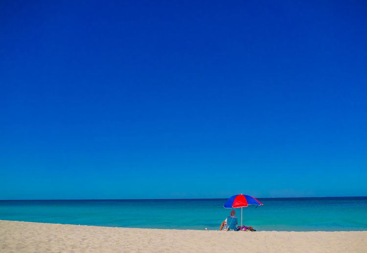 Man Sitting Under Parasol At Beach Against Clear Blue Sky