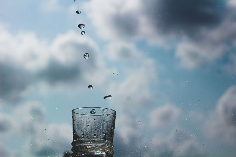 Close-up of water drops on glass against cloudy sky