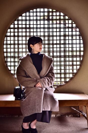 Woman sitting on seat at japanese garden
