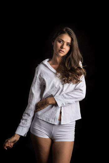 Studio Shot Portrait Beauty Black Background Looking At Camera Three Quarter Length Young Adult One Person Beautiful Woman Long Hair Hair Adult Women Standing Fashion Indoors  Front View Hairstyle Contemplation Shorts