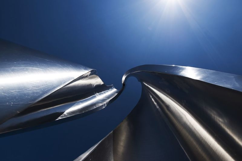 Low Angle View Of Metal Art Against Blue Sky