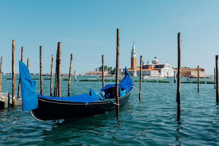 Gondola moored in grand canal by san giorgio maggiore against clear blue sky