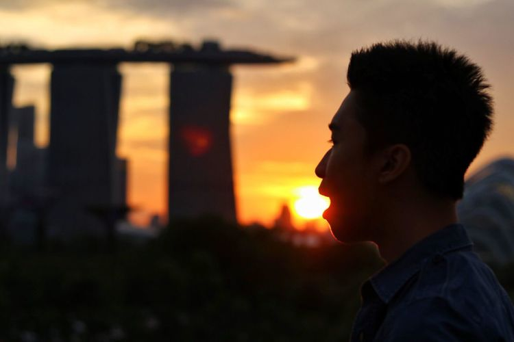 Optical illusion of boy eating sun against sky during sunset at marina bay sands