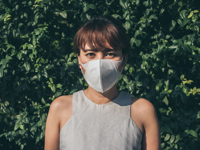 Portrait of woman wearing pollution mask while standing against plants