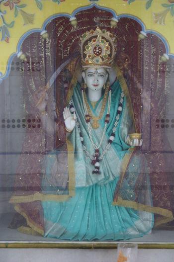 View of buddha statue seen through glass window