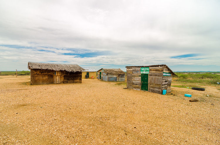 Wooden shacks in a desert in La Guajira, Colombia America Arid Colombia Countryside Dirt Dirty Dry Guajira Horizon Hot House Houses Isolated Land Life Nature Outdoors Poverty Rural Sand Shack Summer Travel Village Waterless