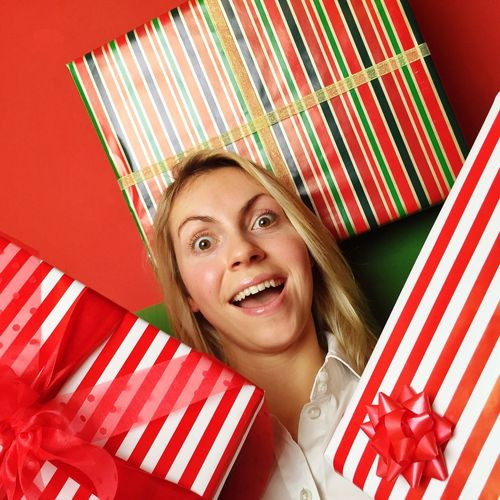 Portrait of a smiling young woman with christmas gifts