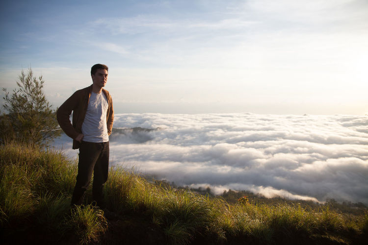 Young man standing on mountains by cloudscape