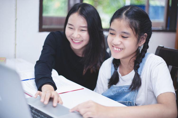Two women sitting in laptop