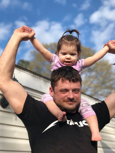 Portrait of father carrying daughter on shoulders outdoors