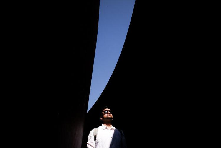 Young man standing below bridge