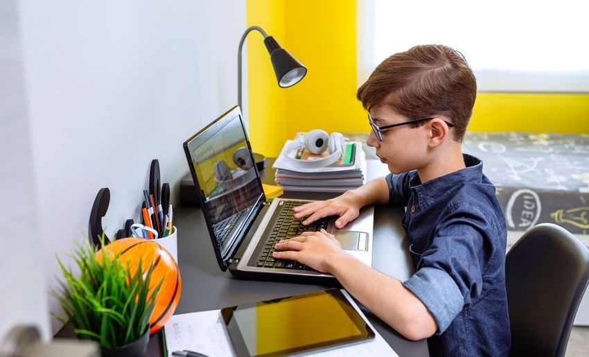 Boy wearing mask studying with laptop at home