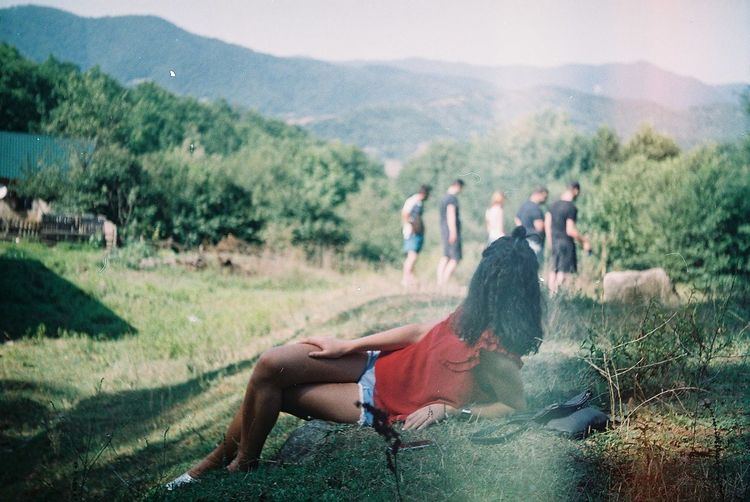 Woman lying on grassy field against mountains