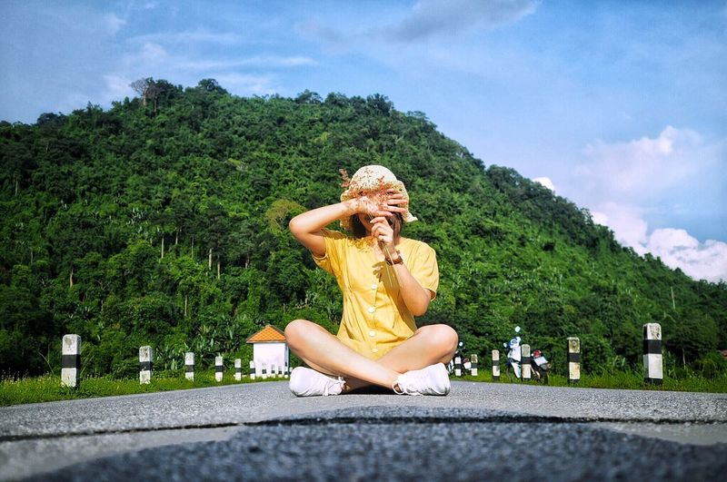 Full Length Of Woman Covering And Holding Stems Over Face While Sitting On Road Against Sky