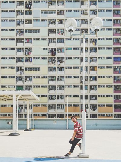 Side View Full Length Of Young Man Standing Against Buildings In City