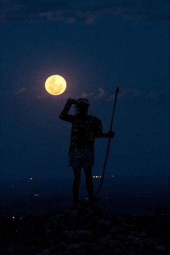 Full length of silhouette man holding illuminated light against sky at night