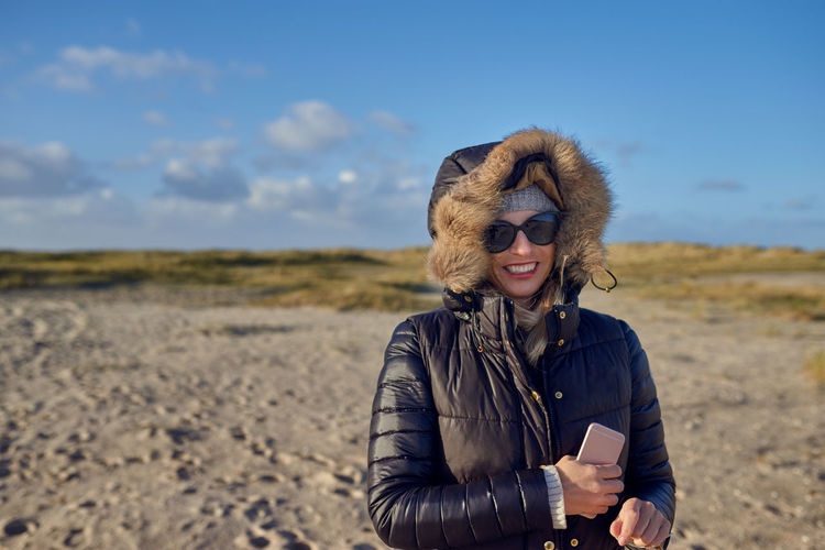 Happy woman walking at the beach Autumn Copy Space Woman Best Ager Day Focus On Foreground Front View Happiness Leisure Activity Lifestyles Middle-aged One Person Outdoors Real People Smiling Standing Upper Body Walking Wireless Technology