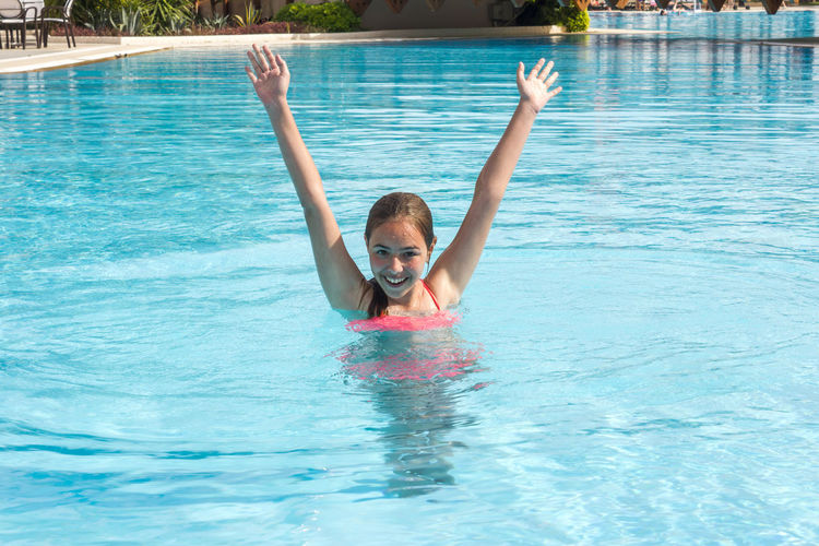 Portrait of girl with arms raised in swimming pool