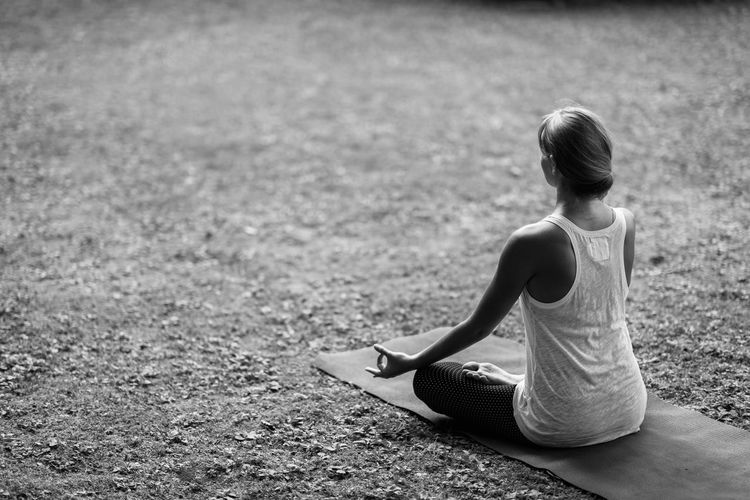 Rear view of young woman meditating in lotus position at park