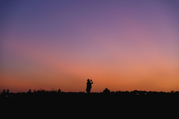 Silhouette of a person standing on a field against sky during sunset