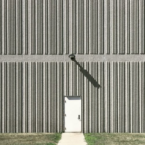 No People Day Outdoors Built Structure Shadow Warehouse Industrial Wall Lines Building Exterior Sunlight Pattern Wall - Building Feature Closed Entrance Building Architecture Protection Industry Door Corrugated Security