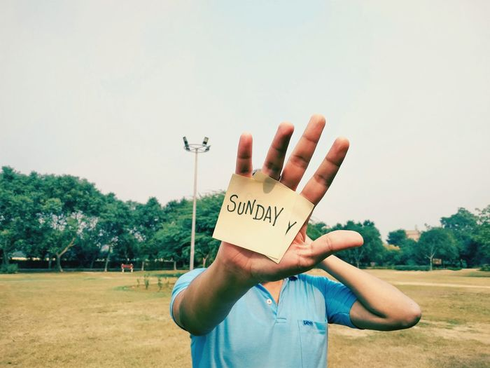 Midsection of person holding text against sky