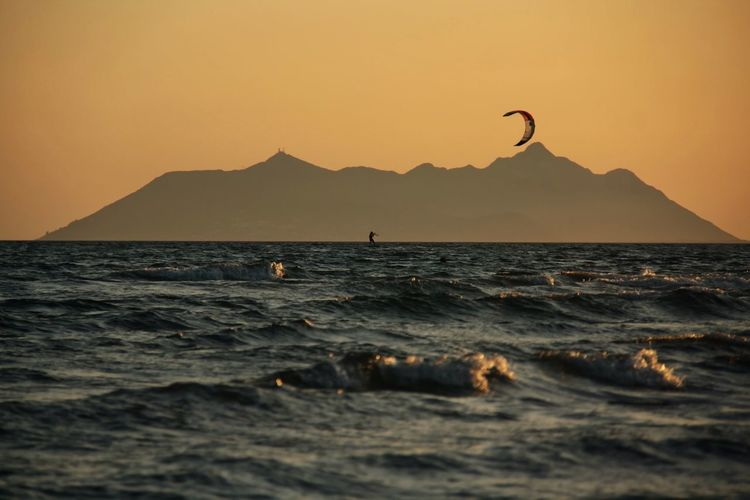 Scenic view of the sea with kite surfer silhouette in the gulf at sunset