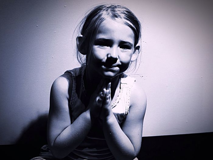 Portrait Of Girl Sitting In Prayer Position Against Wall At Home