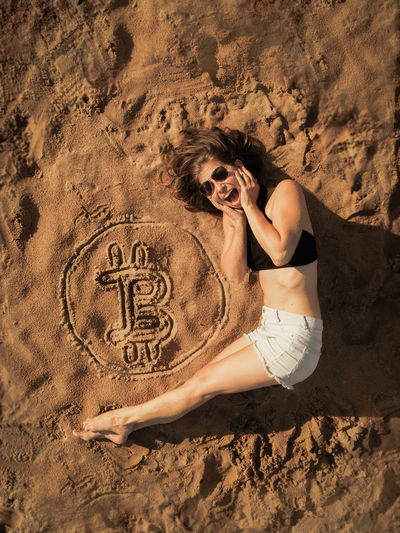Portrait of young woman lying down by bitcoin symbol on sand at beach