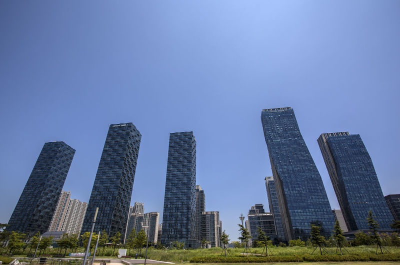 Low Angle View Of Skyscrapers Against Clear Sky Seen From Songdo Central Park