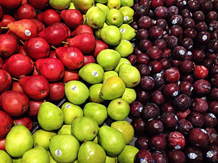 High angle view of fresh pears and apples for sale at market stall