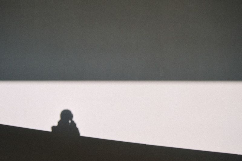 Close-up of woman photographing shadow