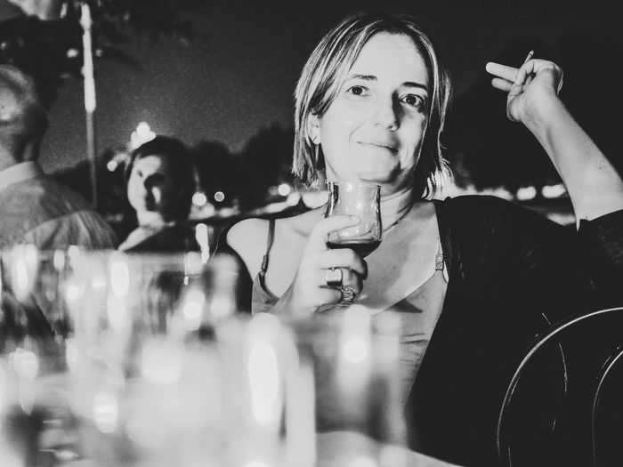 Portrait of woman holding drink while sitting at bar