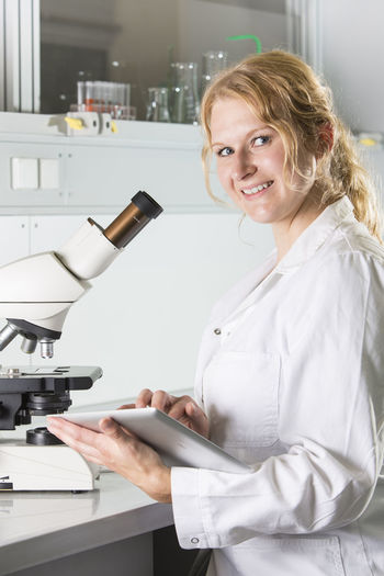 Portrait of smiling woman using digital tablet by microscope on table in laboratory