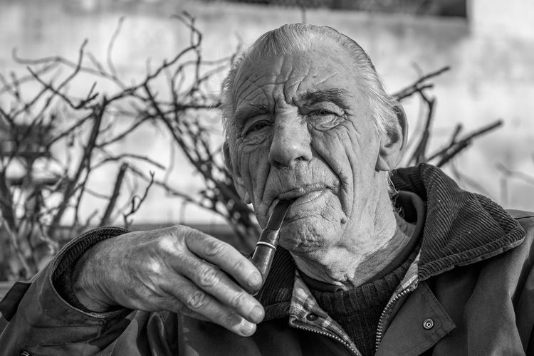 Portrait Of Senior Man Smoking With Pipe Outdoors