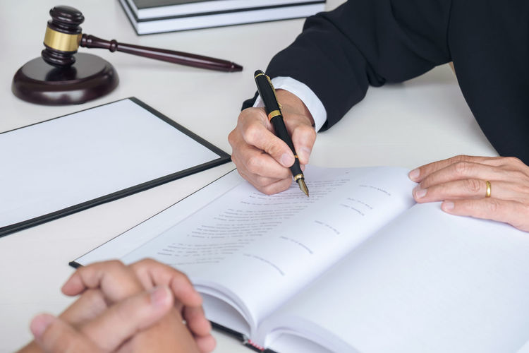 Midsection of lawyer with client doing paperwork in courtroom