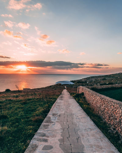 Hagar Qim Beauty In Nature Cloud - Sky Diminishing Perspective Direction Footpath Grass Horizon Horizon Over Water Land Nature No People Outdoors Scenics - Nature Sea Sky Sunset The Way Forward Tranquil Scene Tranquility Water