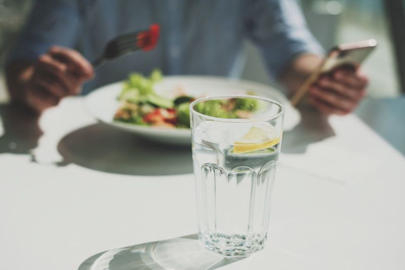 a young man eats a salad in a light restaurant Food And Drink Glass Midsection Refreshment Real People Table Drink Household Equipment Food Lifestyles Holding Indoors  Drinking Glass Hand One Person Freshness Human Hand Focus On Foreground Men