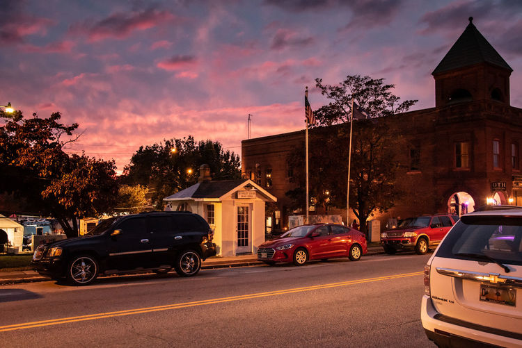 "sunset at ""Pig on Ridge"", the little white house is the smallest police station in the US :) Mode Of Transportation Motor Vehicle Architecture Building Exterior Built Structure Land Vehicle Cloud - Sky Sunset Street Building Incidental People Dusk Tree Sky City Road Car Downtown"