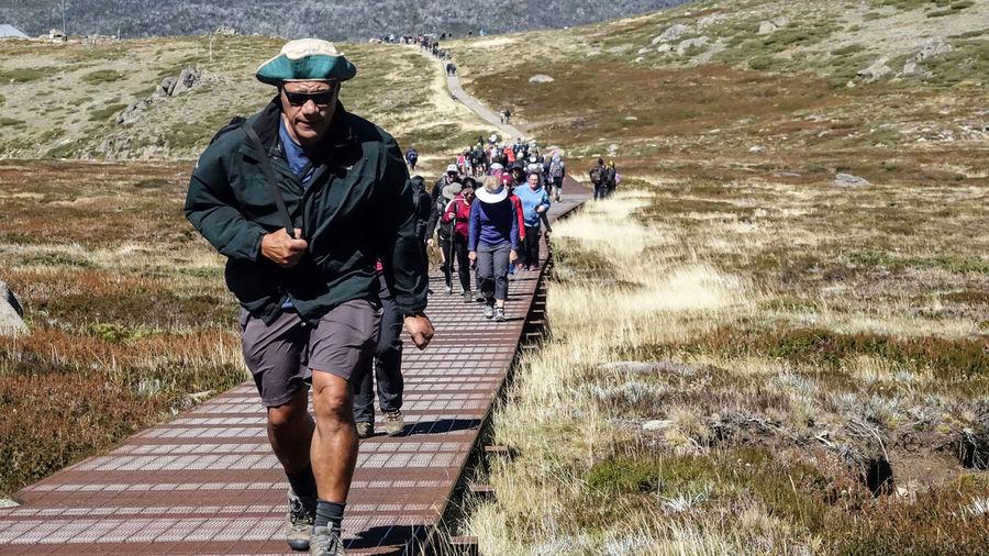 Full length of men walking on footpath
