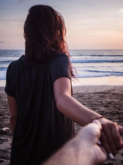 Cropped image of woman and man holding hands at beach
