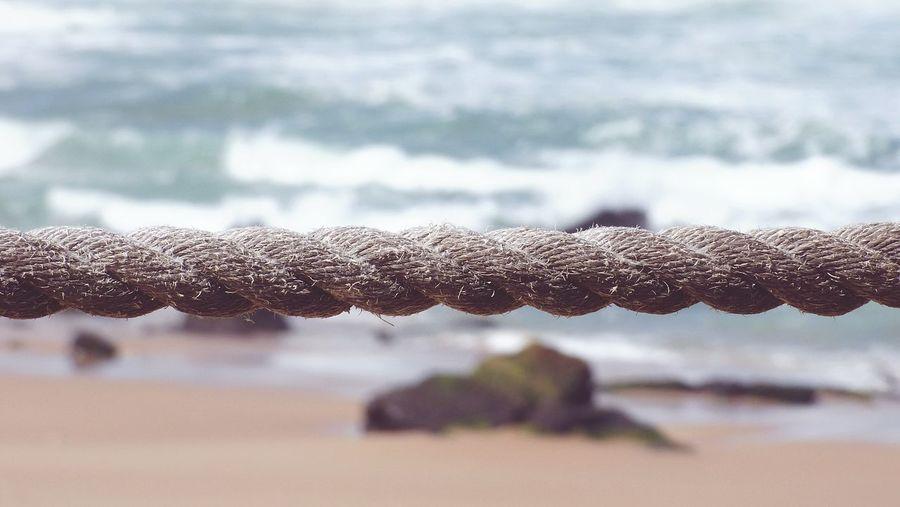 Close-up of rope at beach