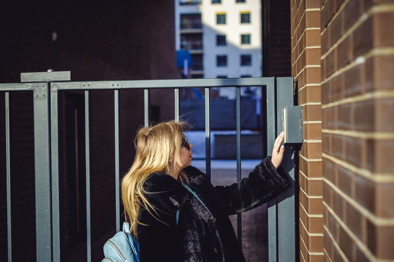 Side view of woman standing by gate
