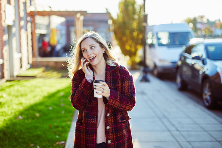Adult Beautiful Woman Blond Hair Car Casual Clothing City Day Focus On Foreground Front View Happiness Holding Leisure Activity Lifestyles Long Hair One Person One Young Woman Only Outdoors Portrait Real People Smiling Standing Technology Wireless Technology Young Adult Young Women