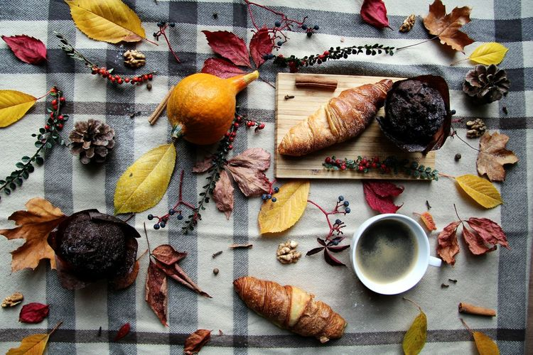 High angle view of coffee with various food and autumn leaves on table