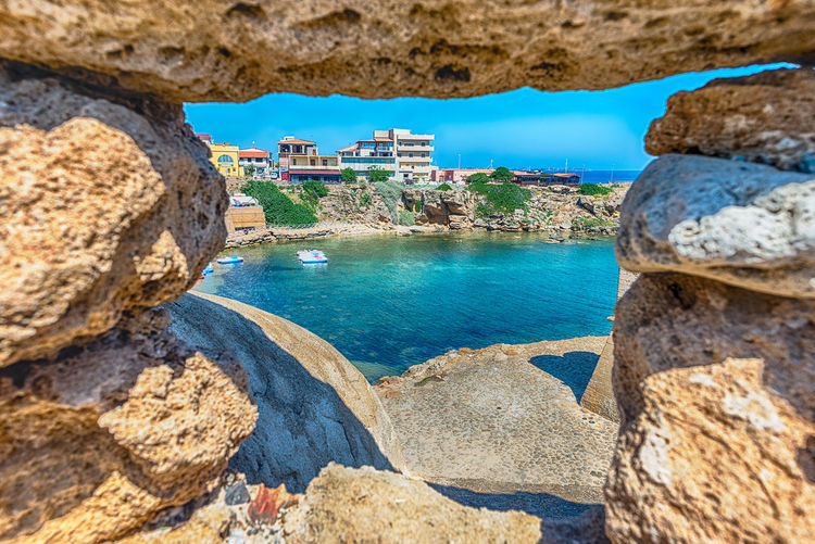 High angle view of rocks by sea against buildings
