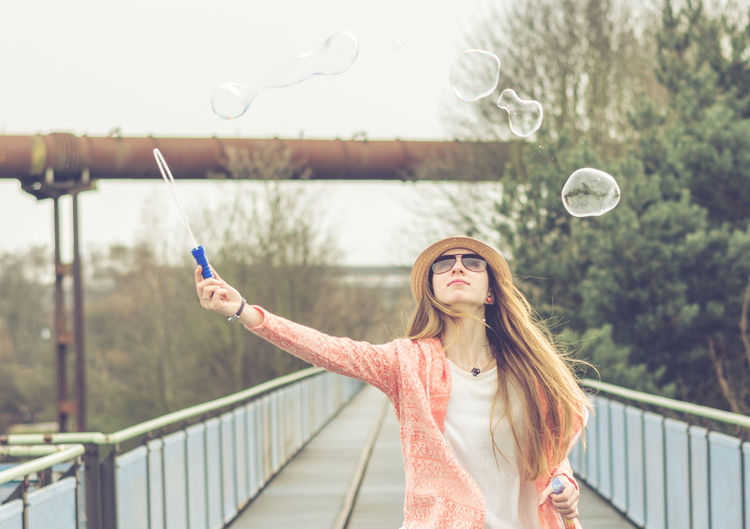 Young woman making bubbles on footbridge