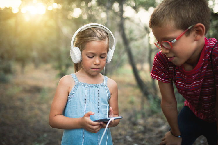 Girl listening music while using mobile phone by brother in forest